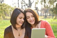 Due belle giovani donne che passano in rassegna una compressa Fotografie Stock