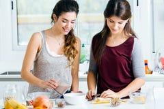 Due belle giovani donne che preparano le ciotole di cereale nella cucina Fotografia Stock
