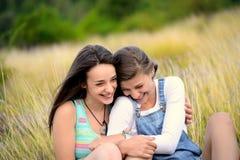 Due belle giovani donne che ridono sull'erba asciutta Fotografia Stock