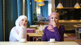 Due belle giovani donne musulmane che ridono e che scherzano mentre sedendosi ad una tavola in un caffè archivi video