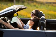 Due belle giovani donne in occhiali da sole stanno sedendo in un cabriolet nero e stanno sorridendo un giorno soleggiato Uno di l fotografia stock libera da diritti