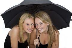 Due belle giovani donne sotto un ombrello fotografia stock libera da diritti