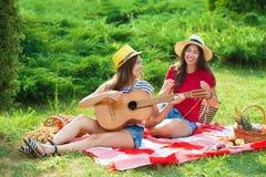 Due belle giovani donne su un picnic che gioca una chitarra e divertiresi Fotografia Stock