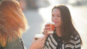 Due belle giovani ragazze alla moda eleganti divertendosi all'aperto Caffè attraente della bevanda delle giovani donne nella citt archivi video