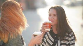 Due belle giovani ragazze alla moda eleganti divertendosi all'aperto Caffè attraente della bevanda delle giovani donne nella citt stock footage