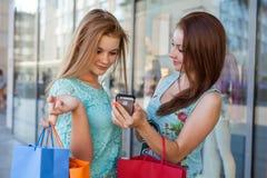 Due belle ragazze con i sacchetti della spesa variopinti ed il telefono cellulare Immagine Stock Libera da Diritti
