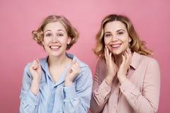 Due belle ragazze dell'amica felicemente e schiacciano entusiasta i loro pugni per preoccuparsi per il loro gruppo favorito immagini stock libere da diritti