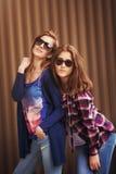 Due belle ragazze felici in occhiali da sole sui precedenti urbani Immagine Stock Libera da Diritti