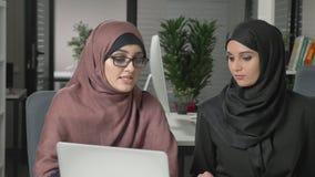 Due belle ragazze nei hijabs si siedono nell'ufficio e discutono i programmi, l'affare, il dialogo, conversazione 60 fps video d archivio