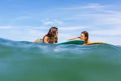 Due belle ragazze sportive che praticano il surfing nell'oceano Fotografia Stock Libera da Diritti