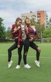 Due belle ragazze sulla posa del campo da giuoco della scuola Immagini Stock Libere da Diritti