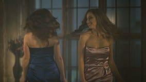 Due belle ragazze in vestiti da sera che filano intorno e che ballano Donna bionda e castana Rosa e vestito lungo blu stock footage