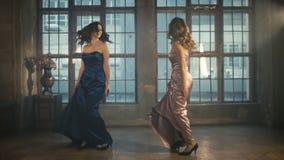Due belle ragazze in vestiti da sera che filano intorno e che ballano Rosa e vestito lungo blu Possibilità remota Biondo e archivi video