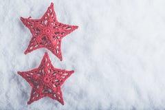 Due belle stelle rosse d'annata magiche su un fondo bianco della neve Concetto di Natale e di inverno Fotografia Stock Libera da Diritti