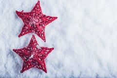 Due belle stelle rosse d'annata magiche su un fondo bianco della neve Concetto di Natale e di inverno Immagine Stock