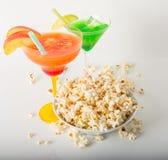 Due bevande di colore, popcorn salato in una ciotola e sparso intorno Fotografia Stock Libera da Diritti