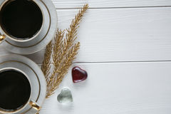 Due bianchi e tazze di caffè dorate con i rami dorati decorativi e piccolo di vetro e due cuori su fondo di legno bianco Fotografia Stock