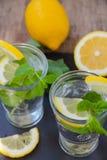 Due bicchieri d'acqua, limone e mente Immagine Stock