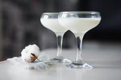 Due bicchieri di latte con un fiore del cotone Immagine Stock Libera da Diritti