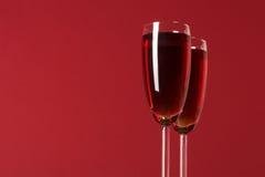 Due bicchieri di vino con vino sui precedenti rossi Fotografie Stock Libere da Diritti