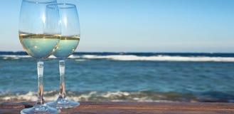 Due bicchieri di vino del vino bianco sopra il fondo del mare Immagini Stock