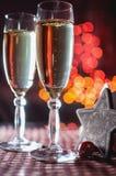 Due bicchieri di vino della stella di legno decorativa del ` s del nuovo anno e del champagne Immagine Stock