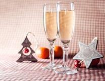 Due bicchieri di vino e decorazioni di Natale sui precedenti a quadretti rossi Immagine Stock