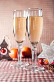 Due bicchieri di vino e decorazioni di Natale sui precedenti a quadretti rossi Fotografia Stock