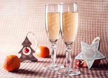 Due bicchieri di vino e decorazioni di Natale sui precedenti a quadretti rossi Fotografia Stock Libera da Diritti