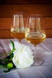 Due bicchieri di vino e fiori della peonia Fotografie Stock