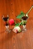 Due bicchieri di vino eleganti e rose delicate del fiore Immagini Stock