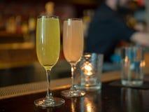 Due bicchieri di vino hanno riempito di bevande della mimosa con la parte posteriore del barista dentro Fotografie Stock