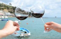 Due bicchieri di vino nelle mani Immagini Stock Libere da Diritti