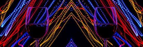 Due bicchieri di vino su un fondo dell'estratto hanno colorato le luci nel moto Linee multicolori di luce su fondo nero fotografie stock libere da diritti