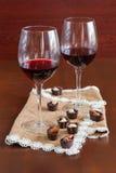 Due bicchieri di vino su una tavola di legno Caramelle Immagini Stock