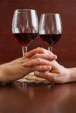 Due bicchieri di vino su una tavola di legno Mani Immagini Stock Libere da Diritti