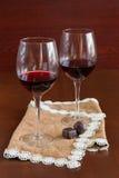 Due bicchieri di vino su una tavola di legno Mani Immagine Stock Libera da Diritti