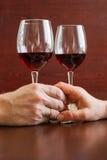 Due bicchieri di vino su una tavola di legno Mani Immagini Stock