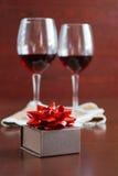 Due bicchieri di vino su una tavola di legno Scatola di Brown con un arco Immagini Stock Libere da Diritti