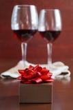 Due bicchieri di vino su una tavola di legno Scatola di Brown con un arco Fotografie Stock
