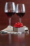 Due bicchieri di vino su una tavola di legno Scatola di Brown con un arco Immagine Stock