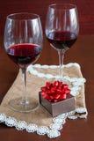 Due bicchieri di vino su una tavola di legno Scatola di Brown con un arco Fotografie Stock Libere da Diritti