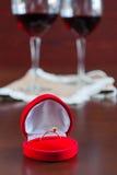 Due bicchieri di vino su una tavola di legno Scatola rossa con l'impegno r Immagine Stock