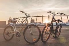 Due biciclette nella città sul tramonto Fotografie Stock