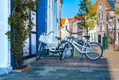 Due biciclette romantiche bianche che stanno vicino ad a vicenda e parcheggiate all'ombra della via Attività esterne Concetto di  immagine stock