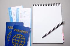 Due biglietti per l'aeroplano con i passaporti ed il taccuino con la penna su fondo grigio Modello Fotografie Stock Libere da Diritti