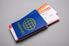 Due biglietti per l'aeroplano con i passaporti su fondo grigio Fotografie Stock