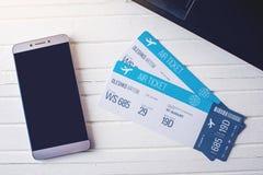 Due biglietti sono sulla tavola con un telefono Concetto di acquisto della prenotazione online del biglietto per il viaggio immagini stock