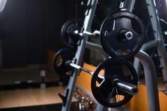 Due bilancieri lunghi su un supporto Supporto del bilanciere su un fondo vago della palestra Teste di legno nere pesanti e enormi fotografia stock
