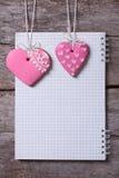 Due biscotti rosa del cuore e una nota su un bordo di legno Fotografie Stock Libere da Diritti
